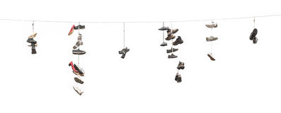 Old worn boots or shoes hang on a cable Royalty Free Stock Image