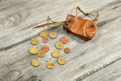 Old worn brown leather coin pouch,  with euro coins spilled on g Royalty Free Stock Photo