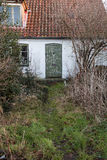 Old Worn Door and Overgrown Garden. Abandoned Ghost House Royalty Free Stock Photography