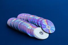 Old DVDs lined up on blue cloth. stock image