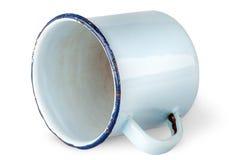 Old worn enameled mug lying. Isolated on white background Royalty Free Stock Images