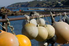 Old worn fishing bouys. In the sun with a Japanese Harbour in the background stock photo