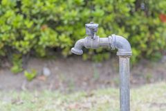 Old and worn garden faucets in the garden. Old and worn garden faucets in the garden royalty free stock photos