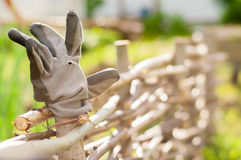 An Old Worn Gardeners Working Glove on a Wicker Fence Royalty Free Stock Photography