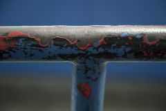 Old and worn handrail with worn out paint. Old handrail showing pitted iron frame and worn out layers of paint royalty free stock image
