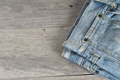 Old worn jeans over a wooden background Royalty Free Stock Image
