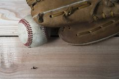 Old worn leather baseball glove and used ball on a wooden Stock Photos