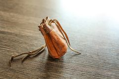 Old worn leather coin pouch on glossy wood desk, white light ref stock photo