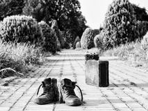 Worn shoes, cardboard suitcase, film camera, brick road. Black-and-white photograph. Royalty Free Stock Photos