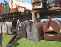 Old worn mail boxes. Close-up of a group of old, worn, and weathered post letter mail boxes stock images