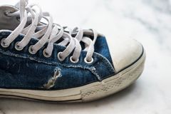 Old worn out blue sneaker. Teenager fashion and lifestyle concept. Used Footwear or shoes for sale in market Royalty Free Stock Image