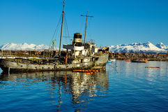Old Worn Out Boat. An old boat with Ushuaia and the mountains of Tierra del Fuego behind it Royalty Free Stock Photo