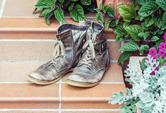 Old worn out boots at doorstep. Pair of old worn out boots at doorstep with plants in background Stock Photo