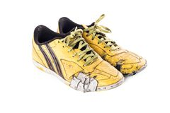 Old  worn out dirty yellow futsal sports shoes  on white background football sportware object isolated