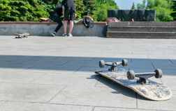 An old worn out skateboard lies on the stone surface of the city cultural monument. An old worn-out skateboard lies on the stone surface of the city`s cultural royalty free stock photo