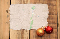 Old worn paper. Christmas balls and old paper on wooden background royalty free stock image