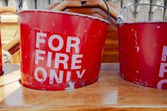 Old and worn red fire buckets in wooden stand royalty free stock images