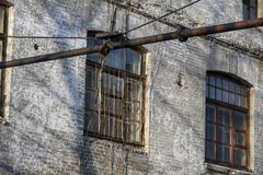 Old worn rounded window with rusty grid in a brick building. Industrial mockup. Vintage effect. stock photos