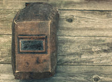 Old, worn, shabby welding mask lying on wooden boards. Stock Images