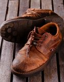 Old worn shoes on grey wooden board Royalty Free Stock Photos