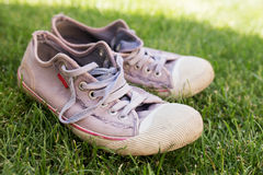 Old worn sneakers. On green grass royalty free stock image