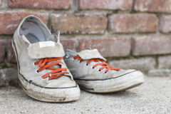 Old Worn Sneakers. Pair of old worn classic sneakers leaning against a brick wall Royalty Free Stock Images