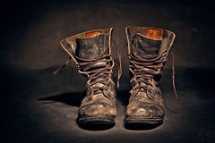 Old worn soldiers work boots. Old soldier's boots worn with scratches and untied shoelaces on white background Royalty Free Stock Images