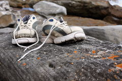 Old worn sports shoes outside. Pair of old worn sports shoes sit on rock Royalty Free Stock Photography