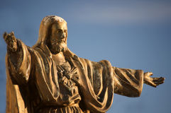 Old, worn statue of Jesus Christ. Against a blue sky Stock Images