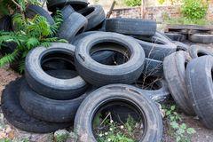 Old worn tires are a big pile in a landfill. Old discarded used tires in a heap. Environmental pollution royalty free stock photo