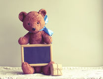 Old worn toy bear with blue bow, photo frame, gift box. On table, retro toned Stock Photo