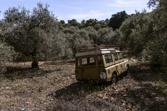 Old worn truck landrover left behind in olive grove. Abandoned and completely worn out old car left behind in the fields stock image