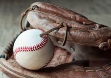 Old and worn used leather baseball sport glove over aged Stock Photography