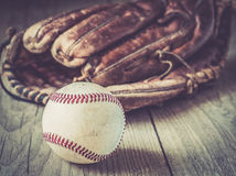 Old and worn used leather baseball sport glove over aged Stock Image