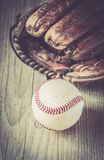 Old and worn used leather baseball sport glove over aged Stock Photos