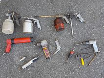 Old worn used tools on ground. Many different old worn used air pressure tools on asphalt ground ground stock photo