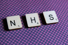 Old worn vintage wooden textured cubes spelling out NHS, the British National health Service,