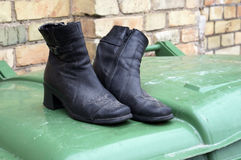 Old worn women`s boots. On the top cover of a city trash can. Poor people and beggars can take away this footwear to themselves royalty free stock image
