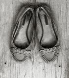 Old worn women's shoes made of genuine leather on old gray wooden board with cracks Stock Image