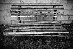 Old worn wooden bench. Black and white, run down, outdoor, worn wooden bench falling apart Royalty Free Stock Images