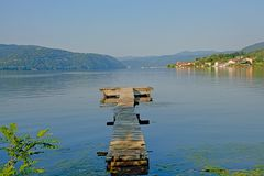 Old worn wooden pier in Danube river in early morning light stock photography