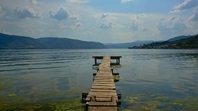 Old worn wooden pier in the rippling water of Danube river stock photo