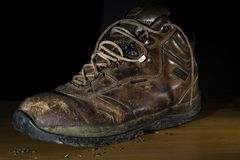 Old Worn Work Boot with Dirt. An old worn work boot with steel toes against a black background stock images