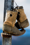 Old Wornout Cowbow Boots. This image shows a pair of old worn out cowboy boots hanging on a metal fence post royalty free stock photos