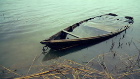 Old wrecked boat on the river bank in spring time. Abandoned fishing boat stock video footage