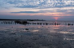 Old wrecked boat with sunset. On the wadden sea, north sea holland Stock Photos
