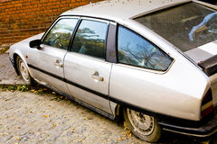 Old wrecked car. Old wrecked gray car on sidewalk stock photo