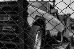 Old wrecked car in black and white scene. Abandoned rusty car in wire fence. Decayed abandoned truck. View from fence to truck. Tr. Agedy and loss. Financial royalty free stock image