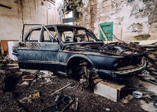 Old wrecked car. Inside of ruinous building royalty free stock images