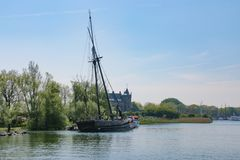 Old wrecked sailing ship on side of river canal. Tall sailing ship wrecked on side of canal river in front of castle under clear blue skies near Amsterdam royalty free stock photography